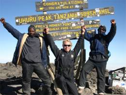 Volunteer celebrating at the top of Mount Kilimanjaro